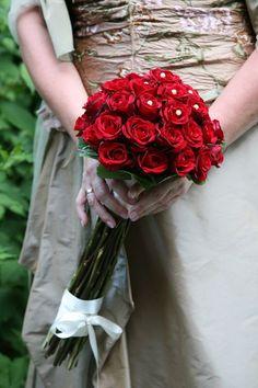 Brautstrauß mit roten Rosen, die mit weißen Perlen verziert wurden.
