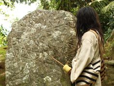 A Kogi Indian stands next to a sacred rock. Many believe that the stone is an ancient indigenous map of the Sierra Nevada that also depicts local river valleys and water systems.