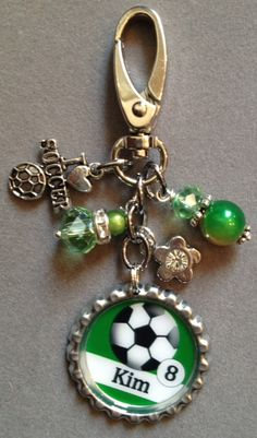 This listing is for one PERSONALIZED SOCCER GIRL BAG BLING!    The bottle cap in this listing is a silver bottlecap. The image will be personalized with the players jersey number and their name. The beads are a mix of green miracle beads and Swarovski crystal beads. It has a soccer charm and a fl...