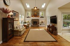 Living space remodeling, Daniels Design and Remodeling, hardwood floors, stone fireplace, tan walls, high ceilings, open space, bright lighting, glass cabinets