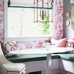 dining rooms - white pink wallpaper white oval dining table white leather chair red piping gray walls red pink pillows L shaped built-in banquette emerald green cushions white roman shade emerald green ribbon trim red lantern