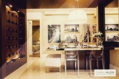 Para este projeto de sala de jantar no bairro Campo Belo, misturamos o clássico da madeira com o moderno do mobiliário e acessórios. O pórtico de MDF com acabamento em Nogueira Catedral ajuda a demarcar o ambiente, e integra a adega com a sala de jantar, que conta com um tampo de vidro na mesa e espelho na parede lateral, para dar amplitude. #camilakleinarquiteta #dinnerroom #saladejantar #adega #interiordesign #decoração