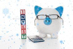 Snow falling against blue and white piggy bank wearing glasses with invest building blocks - Stock Photo - Images