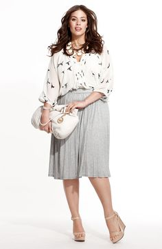 Loose flowing blouse with a high-waist skirt.
