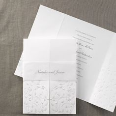 Heart wedding invitations ideas for the bride. Whimsical hearts and flowers add cheer to the front of this folded, bright white invitation that's all wrapped up with a personalized band.  Invitation