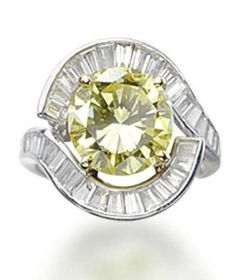 A COLOURED DIAMOND RING, BY TIFFANY & CO.   Centering upon a fancy intense yellow brilliant-cut diamond, weighing 3.81 carats, to the scrolling baguette-cut diamond surround and shoulders, mounted in platinum, size 6¼  Signed Tiffany & Co.