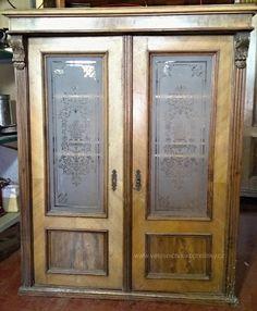 Starožitná prosklená skříň z masivního dřeva s vyřezávanými ornamenty.