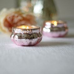 Stunning mercury pink glass tea light holders. These mini tea light holders can be placed on your guest tables, along fire places, window sills and other areas at your wedding venue. They fit a standard size tea light, as the tea light is lit they shine and glimmer giving a warm glow.These tea light holders can also float, fill a vase or bowl with water and float these in the top to create your table centre.Mix and match with our other mercury glass votives and tea light holders to create…