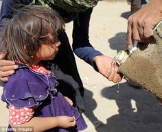 Thirst: A Yazidi child receives long-for water from a jerry can...