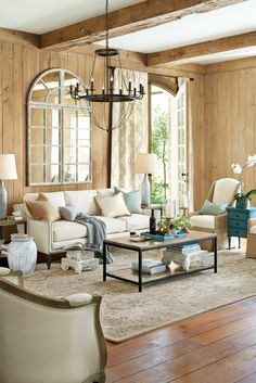 Tan  blue living room- wood walls, beam ceiling, arched window pane mirror, great chandelier and lamps