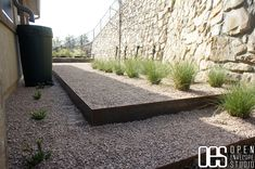 How To Design Charming Landscape Using Pea Gravel Patio: Creative Pea Gravel Patio With Steel Borders And Faux Stone Retaining Walls Plus Shrubs