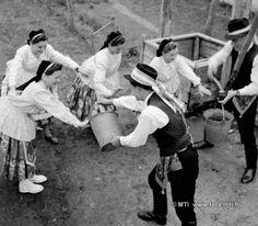 Húsvéti népszokások Miskén. Húsvét hétfőjén  a locsolólegények az udvaron vödörrel öntik a vizet a lányokra 1955
