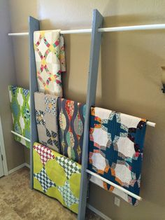 "build a quilt rack (2) 2""x6""x8' (sanded and painted) (3) vinyl coated closet doweling (Home Depot) 1 1/2"" holes drilled 31"" apart 1/4"" angle cut at top and bottom for looks and functionality"