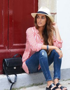 striped blouse. distressed jeans. panama hat. slides.