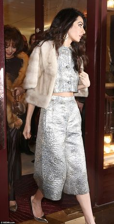 On her way home: Amal wrapped up in a chic fur stole as she left the party