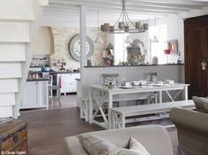 Le coin salle à manger a trouvé sa place contre la cloison-comptoir habillée de lambris blanc.