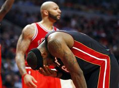 Miami Heat forward LeBron James (front) holds his face after a play as Chicago Bulls forward Carlos Boozer (back) looks on, during the first half of their NBA basketball game in Chicago, Illinois March 27, 2013. REUTERS/Jeff Haynes (UNITED STATES - Tags: SPORT BASKETBALL)