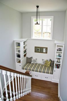 A centrally located stairwell makes this four-square house feel spacious. Interior details such as a daybed, a large window, and bookcases turn a stair landing into a cozy place to read.
