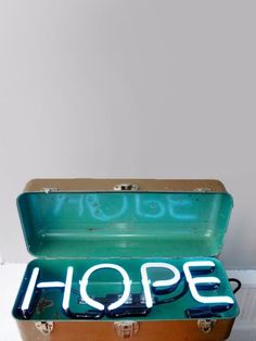 neon hope in a suitcase