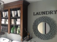 Antique hutch top repurposed as laundry room wall storage....love!