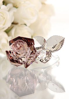 """Swarovski Blossoming Rose   $175.00 3 1/5""""   Item# 1113884  This stunning rose blossom gleams in Crystal Blush with three leaves in Crystal Silver Shade. Its unfaceted clear crystal stem creates a feeling of balance. This timeless and romantic decoration makes the perfect centrepiece for an elegant dinner table.  3 1/5"""" x 3"""""""