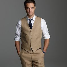 in a fitted vest with rolled sleeves