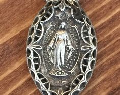 This farm find is a sterling silver Catholic pendant. Here are some details about this item:  - Made sometime during the 19th century. - Oval shape. - Sterling silver (stamped into pendant) - Reads O Mary Conceived without sin pray for us who have recourse to thee - The date 1830 is listed on the front. - No chain is included, just the pendant. - 1 3/4 in length. - 1  in width. - Free Shipping in the U.S.  If you have a question about this item, please send us a message. Thanks~