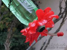 Homemade hummingbird feeder made from plastic water bottle and melted spoons