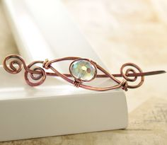 Shawl pin or scarf pin in a swirly eye design with copper and AB finish smoky glass bead