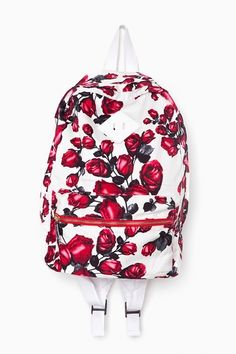 McCarthy Backpack. Features: rose print, front zip pocket with green lining, zip top closure, adjustable padded straps, canvas back.