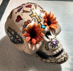 DIY Sugar Skull for Dia de los Muertos / Day of the Dead - plastic skull, fake flowers, glitter glue, and sequins from Dollar Tree; use Sharpies for designs - Dollar Store Craft