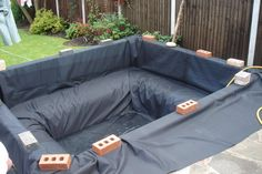 Lee neighbour's koi pond with new pine railway sleepers - The  pond liner goes in