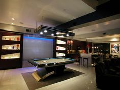 Great room with waterfall behind pool table - kitchen to the left.  Designed by Nancy Hugo CKD