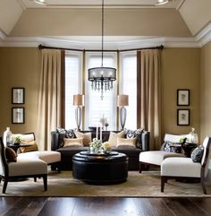 A chic contemporary living room with four plush armless chairs, a chocolate brown leather loveseat and a round ottoman with nailhead trim. The accents in this space are distributed symmetrically for a clean, well-put-together design.
