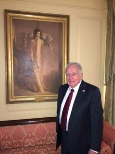 Clint Hill, former Secret Service agent to First Lady Jacqueline Kennedy stands next to her official White House portrait at a 2013 White House holiday party.