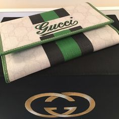 GUCCI 100% AUTHENTIC WALLET GUCCI 100% AUTHENTIC WALLET. WAS A GIFT PURCHASED AT THE GUCCI BOUTIQUE IN BAL HARBOR FLORIDA.  IT IS A LOVELY WALLET IN GREEN WHITE AND BLACK COLORED.  IT HAS CARD HOLDERS INSIDE AND A ZIP POCKET .  THE SIZE IS 6  INCHES WIDE BY 4. INCHES TALL.  A TINY SCUFF IS ON BACK FROM BEING STORED .  THE WALLET HAS NEVER BEEN USED.  NO BOX Gucci Bags Wallets