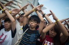 Joshua Wong, centre, a convenor of the student pro-democracy group Scholarism, makes a gesture at the flag-raising ceremony at Golden Bauhin...