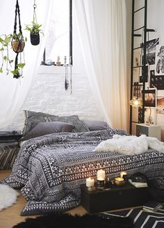 A bohemian bedroom with black and white tons, hanging plants, and lots of photographs on the wall