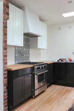 """Tuxedo"" Kitchen - uppers pained BM Simply White, base cabinets are BM Onyx, cement tile backsplash  behind the range 