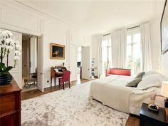 Paris apartment home bedroom with paneled walls, french doors, tall windows, a writing desk and high ceilings