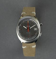 This Omega Geneve Chronostop, manufactured in 1969 is an icon of cool vintage. The grey dial with the silver toned baton markers make a subtle background statement to contrast the red coloured Omega logo and chronostop hand. The outlined date window is positioned at the 3 o'clock position and the fifth-of-a-second timing divisons around the circumference of the dial visually combine with the rare and original Omega steel mesh bracelet. … Read More →
