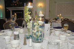 Submerged orchid centerpieces in cylinder vases with aqua blue accent stones and floating candles.