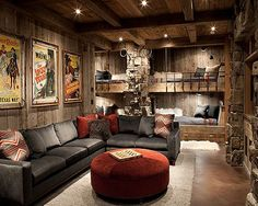Rustic and masculine, this craftsman style space seizes every opportunity for comfort. In this cabin living room natural wood meets tumbled rock for an outdoorsy vibe. These natural materials are accompanied by worn charcoal and brick tones that exude stability and strength.  Recessed bedding adds comfortable versatility to the space, while vintage western film prints add extra color pops and character to the otherwise simple space.