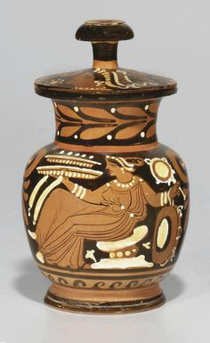 AN APULIAN RED-FIGURED LIDDED MUG  CIRCA 340-320 B.C.  With a draped seated female holding two stacked filled pateras and a fillet in her right hand, a mirror and a tympanum in her left; a band of wave encircling below, laurel on the neck, a large palmette below the handle; the knobbed lid with a female head in profile to the left and a palmette and scrolling tendrils; details in added white and yellow