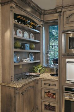 These gray-green kitchen cabinets have a dark glaze on top to mimic years of accumulated dirt, giving this space Old-World appeal.