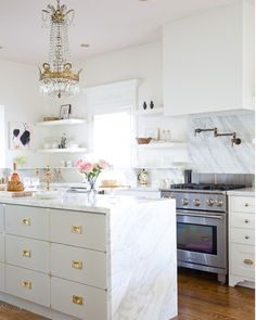 marble waterfall countertops - white kitchen cabinets with brass hardware