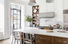 a simple kitchen that incorporates several favorite design elements: white cabinets, marble, steel door and some warm wood tones
