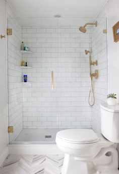Gorgeous all-white bathroom with brass fixtures, built-in corner shelves and a soft gray herringbone patterned floor.