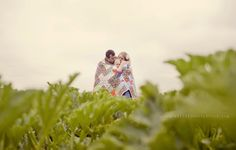 Contrast between green field and sky. Family wrapped in quilt. Snuggled and kisses.