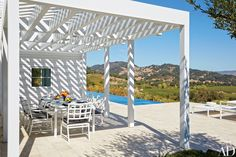 The pergola-covered dining terrace offers bucolic views.